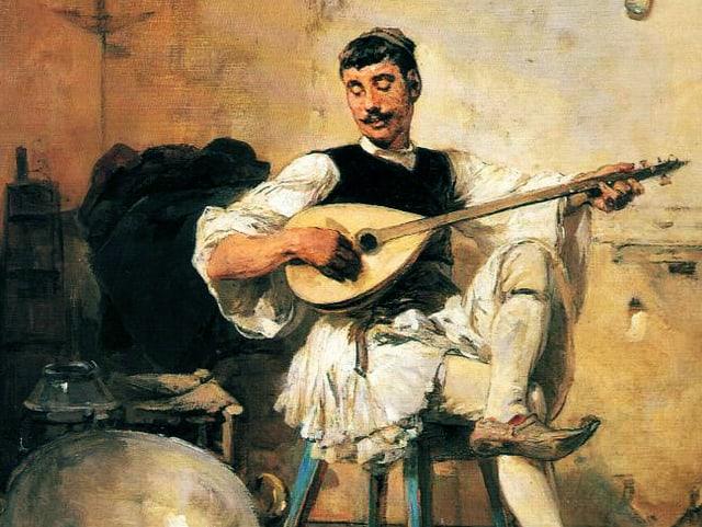 Ein Mann sitz auf einem Stuhl und spielt Busuki.