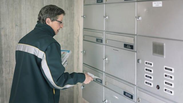 Ein Pöstler verteilt Briefe in Briefkasten