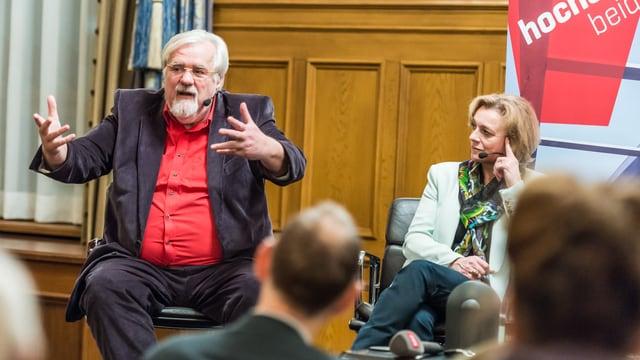 Urs Müller gestukuliert mit beiden Händen, daneben sitzt Kathrin Amacker, schaut ihn an und hört zu.