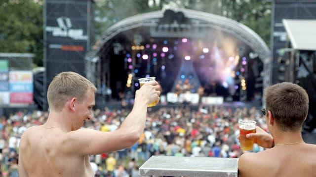 Zwei Männer mit Bierbechern stehen vor eine Bühne mit Musikern.
