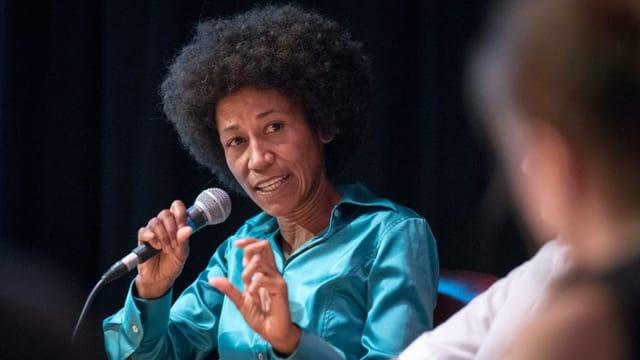 eine Frau redet an einem Podium mit einem Mikrofon