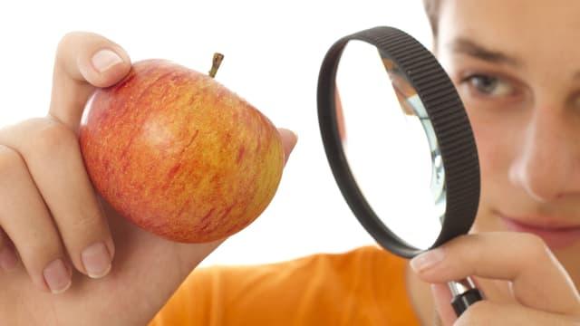 Eine junge Frau schaut sich einen Apfel durch ein Vergrösserungsglas an.