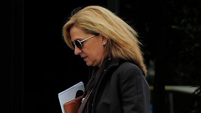 Cristina von Spanien von der Seite mit Sonnenbrille und schwarzem Mantel.
