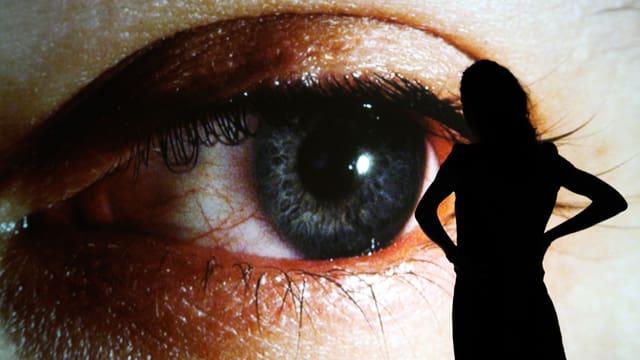 Silhouette einer Frau vor einem überdimensionalen Auge.