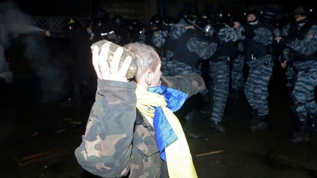 Ein Mann wirft einen Stein auf Poliziisten