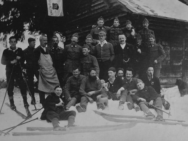 Ein schwarzweiss Foto von einer Gruppe Männern mit Skiern im Schnee.