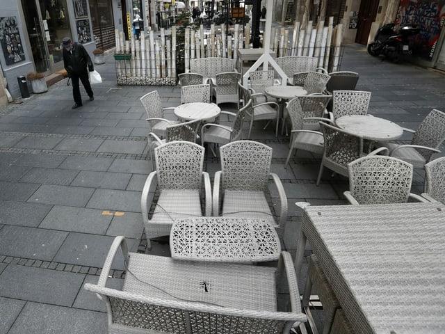Mann mit Atemschutzmaske läuft an aufgestapelten Stühlen vorbei