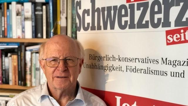 """Ein Mann mit Brille und Halbglatze steht vor einem grossen Banner mit der Aufschrift """"Schweizerzeit""""."""