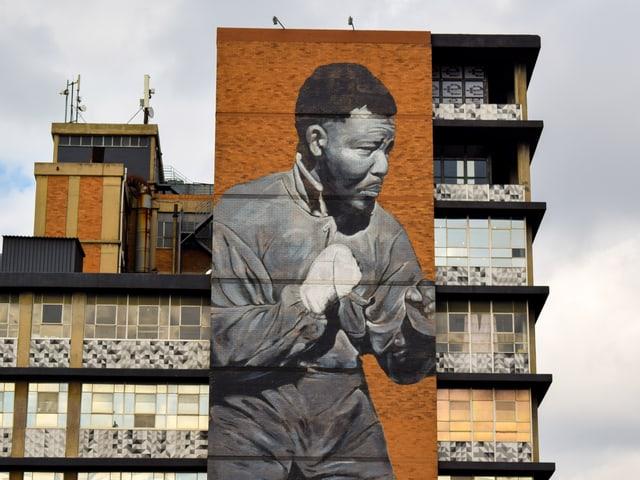 Mural des jungen Nelson Madela mit Boxhandschuhen auf einer Hausfassade.