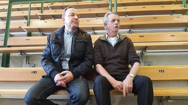 Zwei Männer sitzen auf einer Tribüne