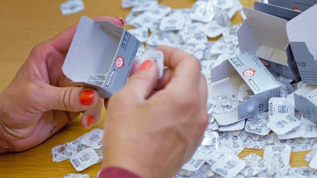 Eine Hand verpackt Kleinigkeiten in Schachteln.