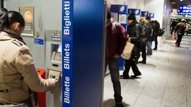 Eine Frau bezahlt ein Billett an einem Automat.