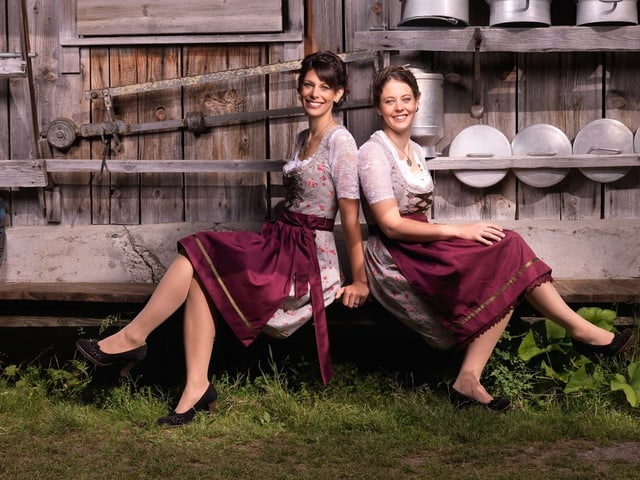 Zwei junge Damen in roten Dirndl vor Stall.