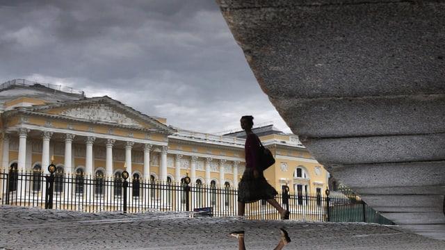 Eine Frau läuft über den Platz vor dem Russischen Museum in St. Petersburg.