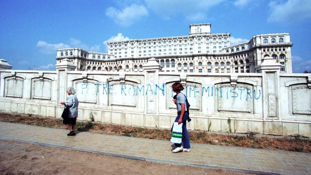 Menschen gehen an einer Mauer vorbei, im Hintergrund ein riesiges, prunkvolles Gebäude.