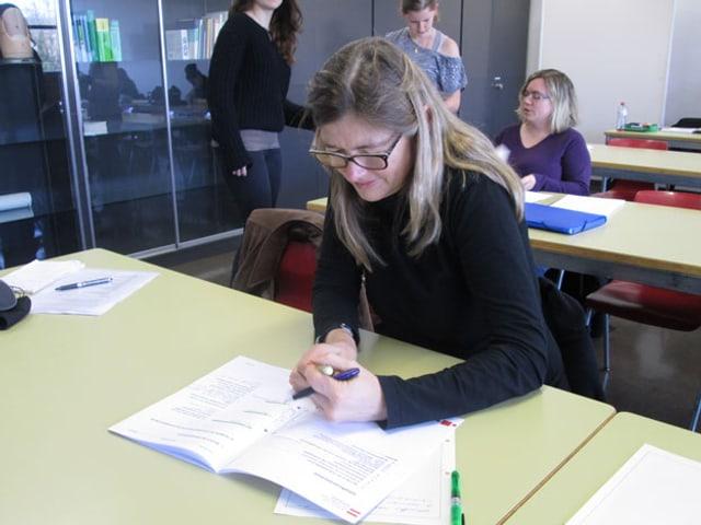 Eine Frau sitzt in einer Schulbank und macht sich Notizen.