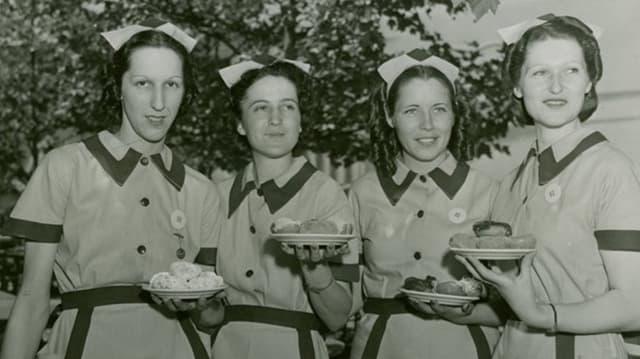 Vier Frauen halten Teller mit Doughnuts in den Händen