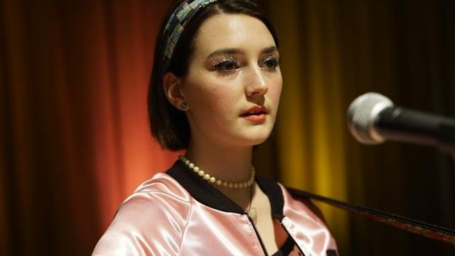 Eine junge Frau steht vor dem Mikrofon.