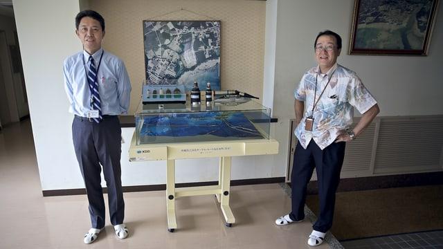 Die beiden Manager posieren vor einem Modell und Kabel-Querschnitten.