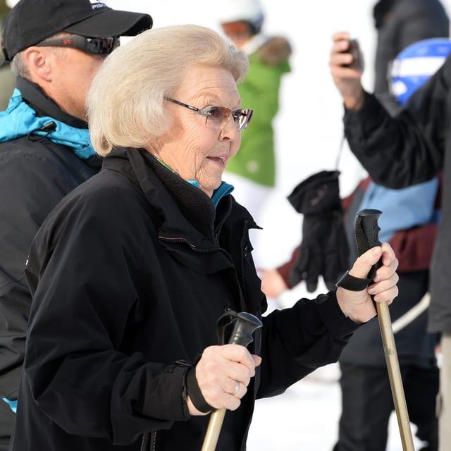 Königin Beatrix mit Skistöcken und schwarzer Winterjacke.