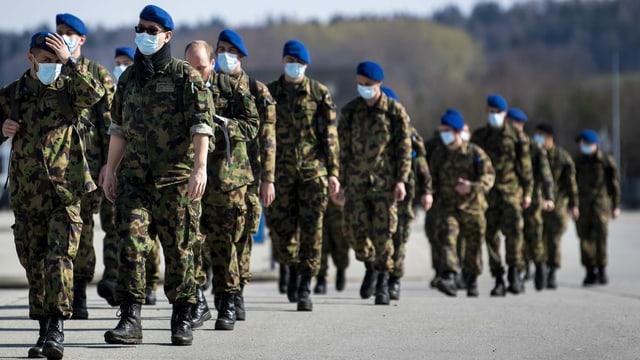 Purtret da militarists che portan mascras da protecziun.