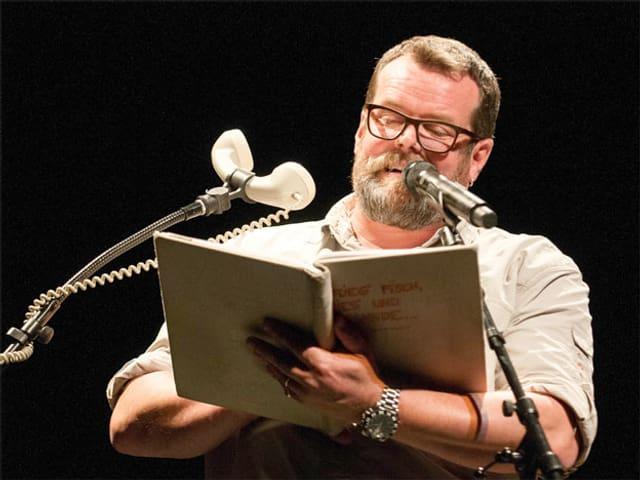 Mann mit Buch vor Mikrofon und Telefonhörer.