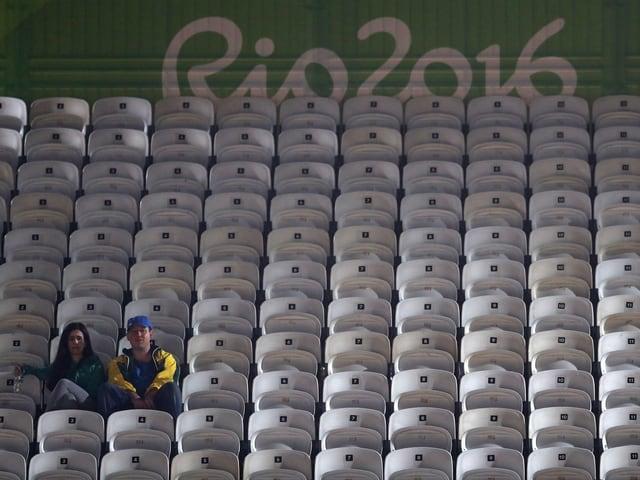 Sitzleder: Zwei Zuschauer beim Beachvolleyball Match Canada – Lettland machen den Sieg im Dauer-Stillsitzen unter sich aus. Und wenn sie nicht gestorben sind…