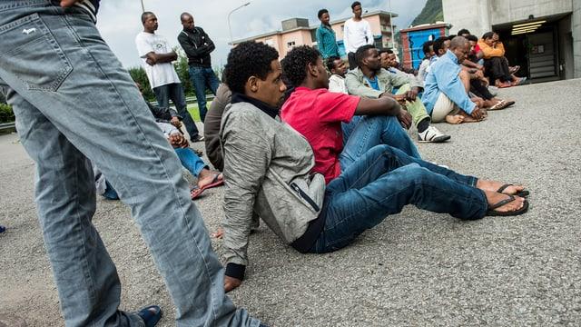 Eritreer sitzen auf einem asphaltierten Vorplatz vor einer Zivilschutzanlage.