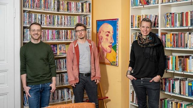 drei Menschen stehen vor einem grossen Bücherregal