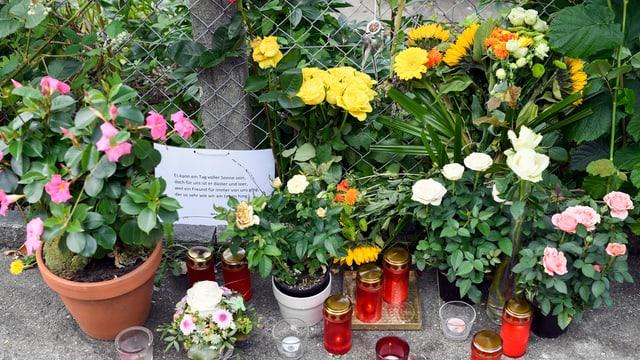 Blumen und Kerzen stehen auf dem Boden.