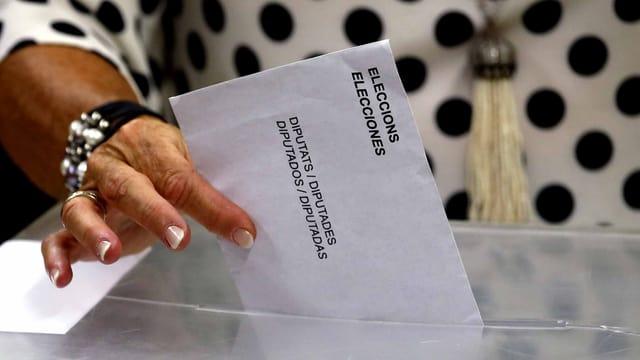 Eine Frauenhand wirft den Wahlzettel in die Urne.