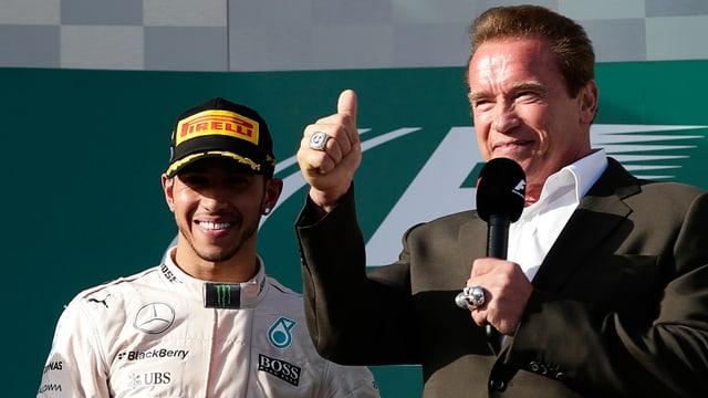 Lewis Hamilton steht neben Arnold Schwarzenegger, der den rechten Daumen in die Luft reckt.