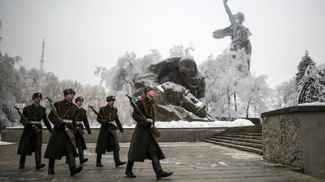 Sicherheitskräfte marschieren an einer Statue in Wolgograd vorbei. Sie tragen lange Mäntel und Stiefel.