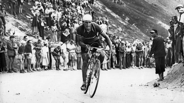 Schwarzweissbild: Bartali auf dem Rennrad auf einer Bergstrasse. Am Strassenrande zahlreiche Zuschauer.