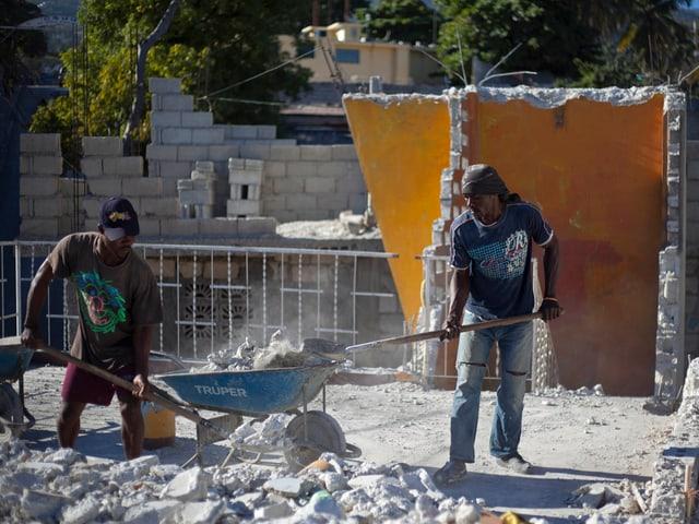 Arbeiter aus Haiti bauen ein Haus wieder auf.