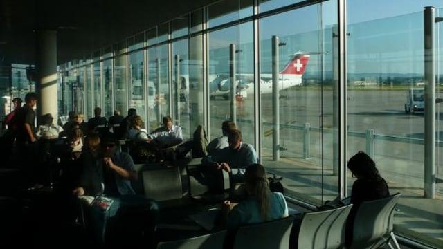 Wartehalle mit sitzenden Passagieren, durch die Scheibe ist ein Flugzeug der Swiss sichtbar.