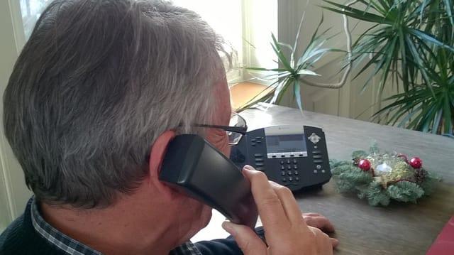 Ein Mann sitzt am Tisch und telefoniert