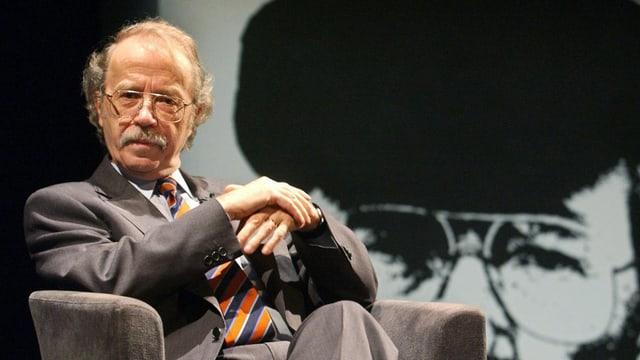 Der Autor sitzt mit übereinander gefalteten Händen auf einem Sessel. Hinter ihm ist eine grosse Leinwand mit einem Foto von ihm zu erkennen.