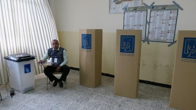 Ein Wahlhelfer sitzt neben Wahlkabinen ohne Personen.