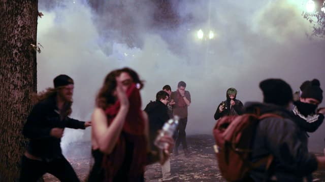 Protestas a Portland en l'Oregon - persunas fugian dal gas lacrimogen.