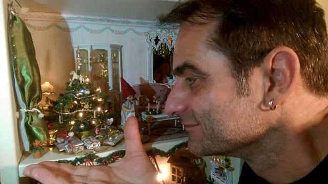 Thomy Scherrer hält seine Hand unter einen Miniatur-Weihnachtsbaum.