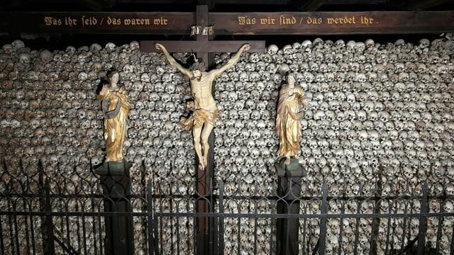 Unzählige, aufeinandergsetapelte Totenschädel. Davor Christuskreuz, darüber ein Holzbalken mit Inschrift.