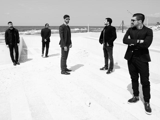 Fünf junge Männer stehen am Strand.