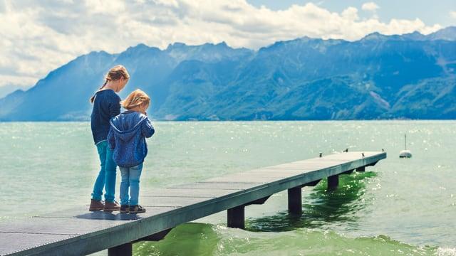 Zwei Kinder stehen auf einem Steg am Wasser.