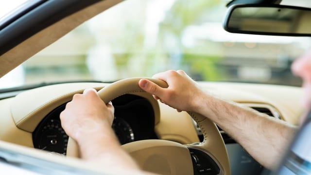 Hände an Autokenkrad