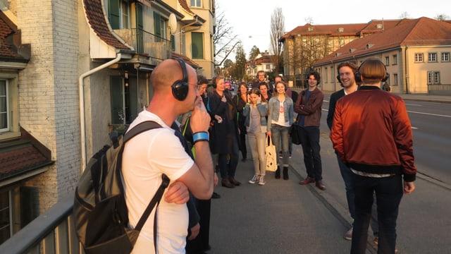 Gruppe mit Kopfhörern auf einem Trottoir.