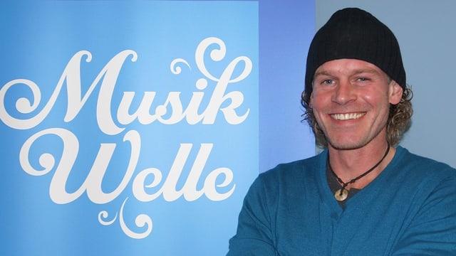 Ein lachender Mann mit blauem Pullover und schwarzer Mütze.