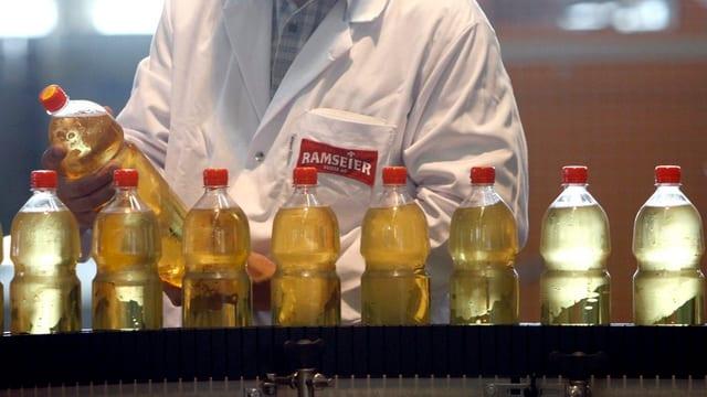 Fliessband mit Plastikflaschen. Im Hintergrund sieht man einen weissen Kittel mit der Aufschrift Ramseier.