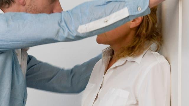 Ein Mann mit hellblauem Hemd bedrängt eine Frau mit einer weissen Bluse.