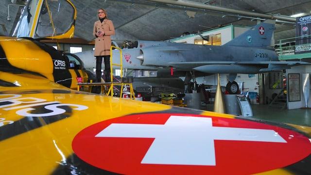 Moderatorin Sonja Hasler steht auf dem Flügel eines Kampfjets